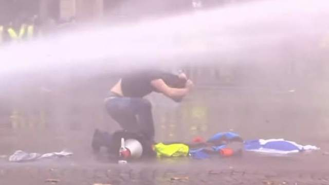 Protester dodge the water cannon spray.