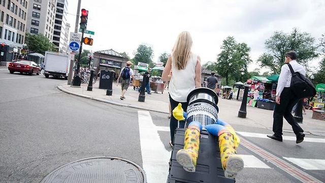 HitchBOT riding on a suitcases in Boston