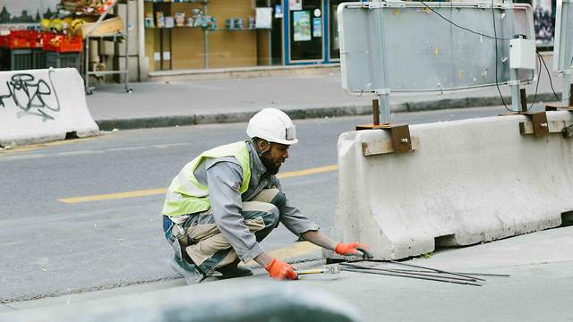 A man working construction on a road