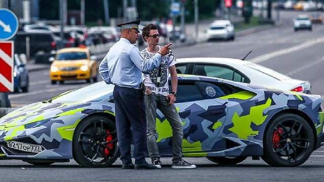 Alleged Evil Corp mastermind Maksim Yakubets stands next to his Lamborghini Huracan.